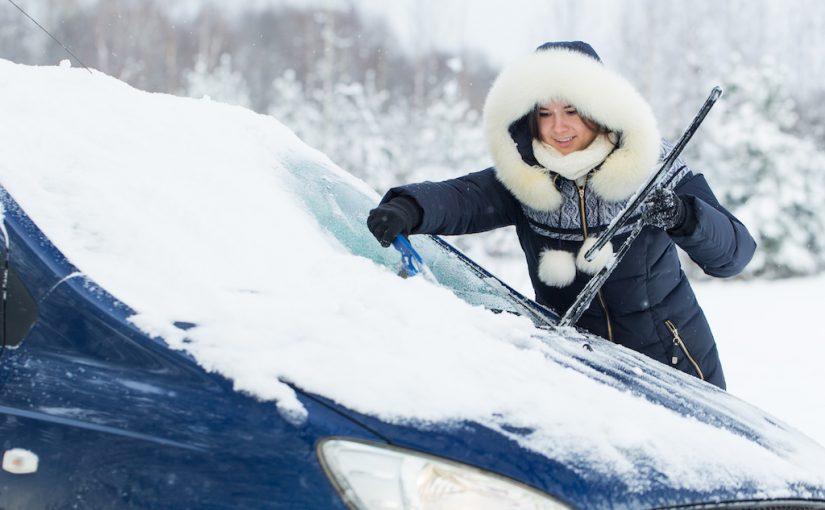 雪が積もった車を掃除する女性
